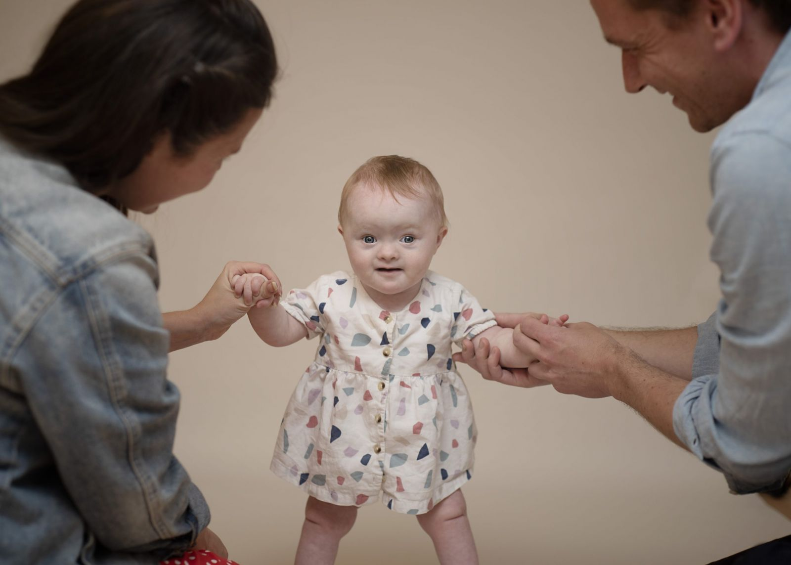 baby first year photoshoot holding hands mum and dad